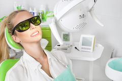 Ung härlig kvinna med härliga vita tänder som sitter på en tand- stol arkivfoton