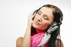 Ung härlig kvinna med hörlurar som tycker om musiken Royaltyfri Fotografi