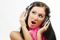 Ung härlig kvinna med hörlurar som tycker om musiken Arkivfoton
