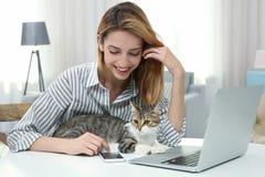 Ung härlig kvinna med katten genom att använda bärbara datorn arkivbild