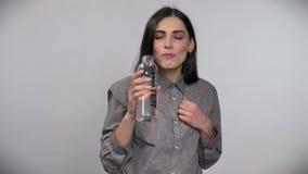 Ung härlig kvinna med kort brunt hår som dricker från flaskan med vatten och ler, vit bakgrund arkivfilmer