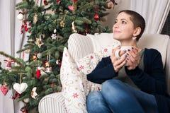 Ung härlig kvinna med kort hår som tycker om kopp te som framme sitter av julträd Arkivbilder