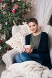 Ung härlig kvinna med kort hår som tycker om kopp te som framme sitter av julträd Arkivfoto