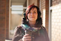 Ung härlig kvinna med kort röd hår och hörlurar med kaffe som går kopp royaltyfri bild
