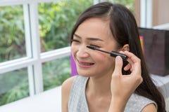 Ung härlig kvinna med makeupborsten Två vänner som utgör i kafét asiatisk flicka Vänner är mascaraborsten royaltyfria bilder