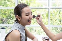 Ung härlig kvinna med makeupborsten Vänner som gör smink i en coffee shop royaltyfri bild