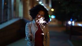 Ung härlig kvinna med mycket lockig afro hårdans med bengal brand på den upplysta gatan för natt Ovanligt moderiktigt lager videofilmer