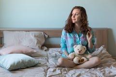 Ung härlig kvinna med nallebjörnen i säng Arkivbild