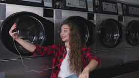 Ung härlig kvinna med rött lockigt hår i röd tartainskjorta Lyssna till musiken som talar vid telefonen Dans i tvätteri arkivfilmer