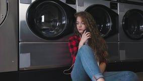 Ung härlig kvinna med rött lockigt hår i röd tartainskjorta Lyssna till musiken som talar vid telefonen Dans i tvätteri lager videofilmer