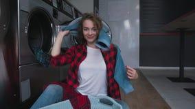 Ung härlig kvinna med rött lockigt hår i röd tartainskjorta satt kläder som tvättar mashine Dans i tvätteri lager videofilmer