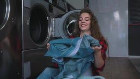 Ung härlig kvinna med rött lockigt hår i röd tartainskjorta satt kläder som tvättar mashine Dans i tvätteri stock video