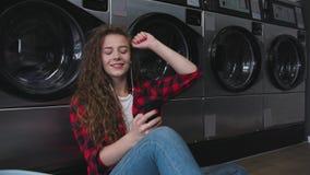 Ung härlig kvinna med rött lockigt hår i röd tartainskjorta satt kläder som tvättar mashine Dans i tvätteri långsamt stock video