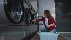 Ung härlig kvinna med rött lockigt hår i röd tartainskjorta satt kläder som tvättar mashine i Loundry lager videofilmer