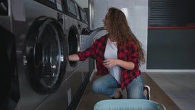 Ung härlig kvinna med rött lockigt hår i röd tartainskjorta satt kläder som tvättar mashine i Loundry Infdoor stock video