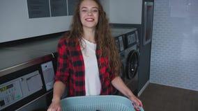 Ung härlig kvinna med rött lockigt hår i röd tartainskjorta satt kläder som tvättar mashine i Loundry Infdoor långsamt stock video