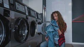 Ung härlig kvinna med rött lockigt hår i röd tartainskjorta satt kläder som tvättar mashine i Loundry Infdoor långsamt lager videofilmer