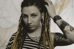 Ung härlig kvinna med tatueringen och dreadlocks Arkivfoto