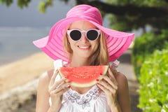 Ung härlig kvinna med vattenmelon som bär rosa sunhat och su Fotografering för Bildbyråer