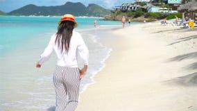 Ung härlig kvinna på den tropiska kusten Lycklig flickabakgrund den blåa himlen och turkosen bevattnar i havet på arkivfilmer