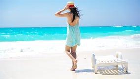 Ung härlig kvinna på den tropiska stranden för vit sand Tillbaka sikt av den caucasian flickan i hattbakgrund havet arkivfilmer