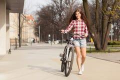 Ung härlig kvinna på en cykel Arkivbild