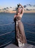 Ung härlig kvinna på en träplattform över havet Arkivbild