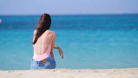 Ung härlig kvinna på stranden under tropisk semester Flickan tycker om hennes wekeend på en av de härliga stränderna in lager videofilmer