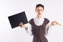 Ung härlig kvinna på vit isolerade bakgrundshålldokument och linjal, lärare arkivbild