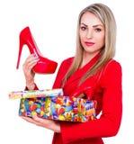 Ung härlig kvinna som är lycklig att motta röda skor för höga häl som en gåva Royaltyfria Foton