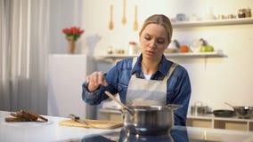 Ung härlig kvinna som är olycklig med att laga mat i kök som är uttråkad och som är trött av sysslor arkivfilmer