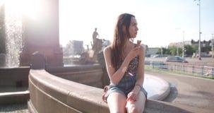 Ung härlig kvinna som äter glass under solig dag, utomhus Fotografering för Bildbyråer