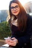Ung härlig kvinna som använder hennes mobiltelefon i gatan Fotografering för Bildbyråer