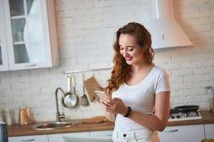 Ung härlig kvinna som använder hennes smartphone, medan laga mat i det moderna köket Sunt mat- och bantabegrepp f?rlorande vikt royaltyfri foto