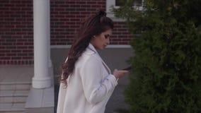 Ung härlig kvinna som använder hennes utomhus- mobiltelefon stock video