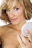 Ung härlig kvinna som applicerar makeup arkivfoto