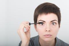 Ung härlig kvinna som applicerar mascara på ögon Skönhetsmink Ståenden av flickan med fejkar ögonfrans som applicerar svart Royaltyfria Bilder