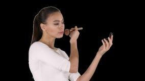 Ung härlig kvinna som applicerar pulver på kind med borsten, Alpha Channel stock video