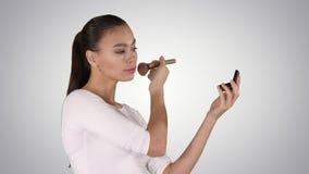 Ung härlig kvinna som applicerar pulver på kind med borsten på lutningbakgrund stock video