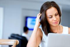 Ung härlig kvinna som arbetar på hennes bärbar dator royaltyfria bilder