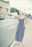 Ung härlig kvinna som försöker att välkomna en taxi i staden Fotografering för Bildbyråer