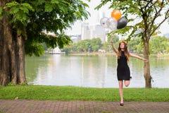 Ung härlig kvinna som firar avläggande av examen på parkera i smäll Royaltyfria Bilder
