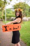 Ung härlig kvinna som firar avläggande av examen på parkera i smäll Arkivbilder