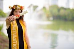 Ung härlig kvinna som firar avläggande av examen på parkera i smäll Arkivfoton