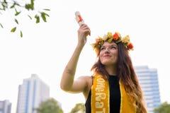 Ung härlig kvinna som firar avläggande av examen på parkera i smäll Arkivfoto