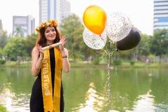 Ung härlig kvinna som firar avläggande av examen på parkera i smäll Royaltyfri Bild