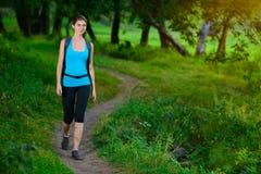 Ung härlig kvinna som fotvandrar i den gröna sommarskogen Arkivfoto
