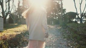 Ung härlig kvinna som går i delen på den ljusa soliga dagen Kvinnligvänd och leende till något, lyckliga blickar Arkivbild