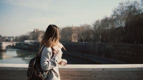 Ung härlig kvinna som går i den soliga morgonen på bron Attraktivt kvinnligt dricka kaffe och har en promenad Royaltyfri Foto