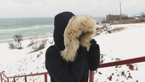 Ung härlig kvinna som går runt om stranden på en kall vinterdag långsam rörelse lager videofilmer
